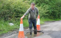 Councillor Anthony Feely stands in a deep pothole on the Tully Road, Garrison