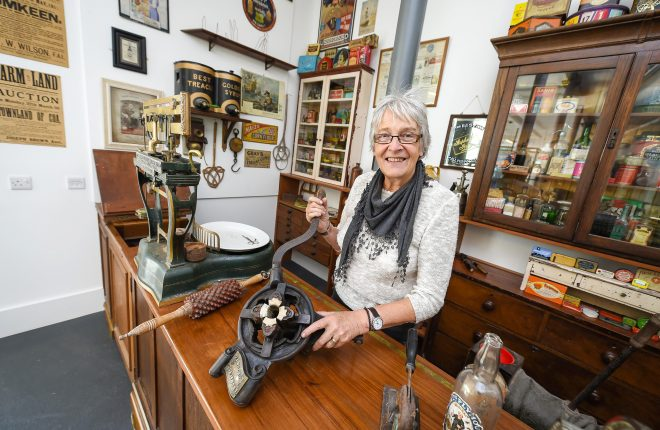 Toni Johnson, wife of the late Gordon Johnson, donated a large part of their collection to the museum.  Here she is pictured with a clamp for attaching silver foil to wine bottles    RMG84
